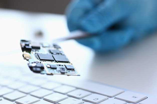 コンピュータ修理サービスアセンブリの従業員は、はんだ付け技術開発の方法を使用して、取り付け用のスペアパーツマザーボードプロセッサをピンセットで保持します Premium写真