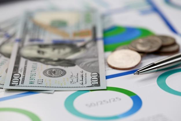 Серебряная ручка лежа на графиках доллара наличных денег стола в установке домашнего офиса. расчет семейных расходов социальный доход внештатный сотрудник и концепция исследования роста ситуации Premium Фотографии