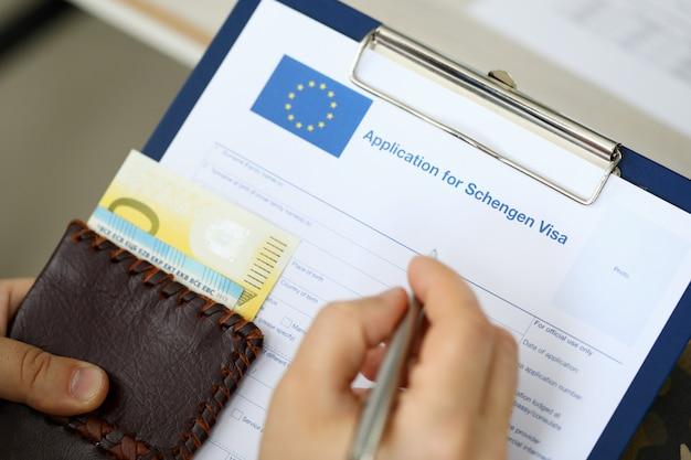 お金を保持しながらシェンゲンビザの書類に記入する男の平面図。旅行のコンセプト Premium写真
