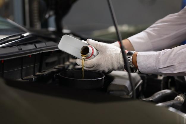 Сосредоточиться на мужской специалист руки, держа канистру машинной жидкости Premium Фотографии