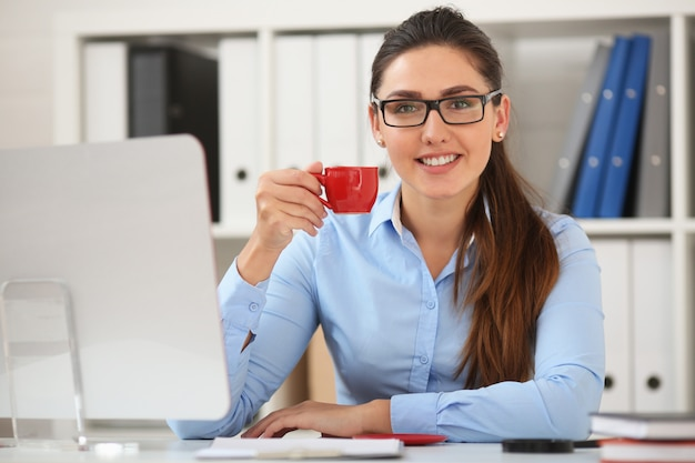 ビジネスの女性は、赤いマグカップからテーブルでオフィスでコーヒーを飲む Premium写真