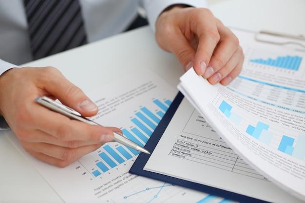 Мужские руки, держа финансовые документы Premium Фотографии