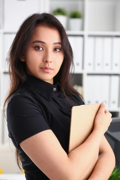 Брюнетка женщина, держащая буфера обмена Premium Фотографии