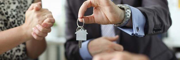 全米リアルター協会加入者の手が家の鍵のアガニストオフィスを保持します。 Premium写真