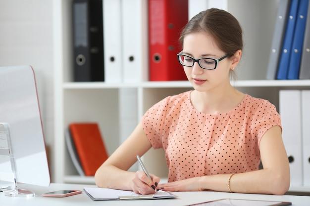 オフィスの女性は日記にメモを取る Premium写真