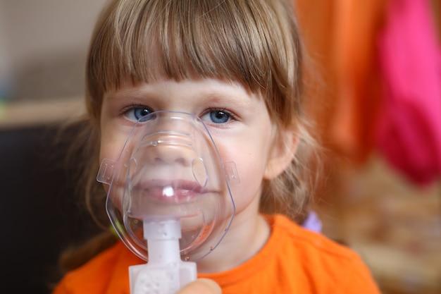 Счастливый ребенок делает ингаляцию дома для Premium Фотографии