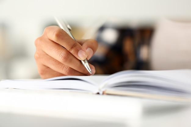 黒人女性の腕はノートに物語を書きます Premium写真