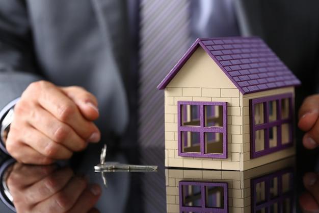スーツとネクタイの男は手に銀のキーを与える Premium写真
