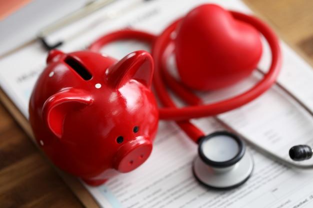 赤い貯金の聴診器と健康保険請求申請フォームのクローズアップで横になっているおもちゃの心 Premium写真