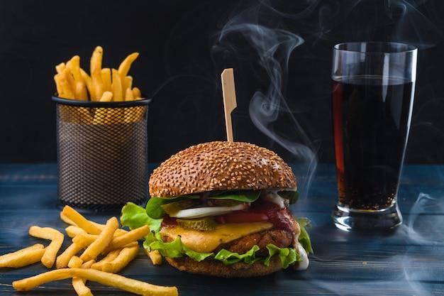 フライドポテトと木製のテーブルでドリンクベジタリアンハンバーガー Premium写真