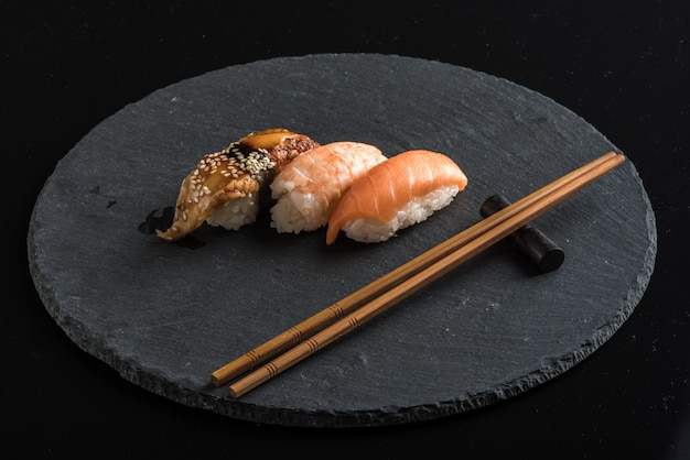 Суши на черной каменной тарелке с палочками для еды Premium Фотографии