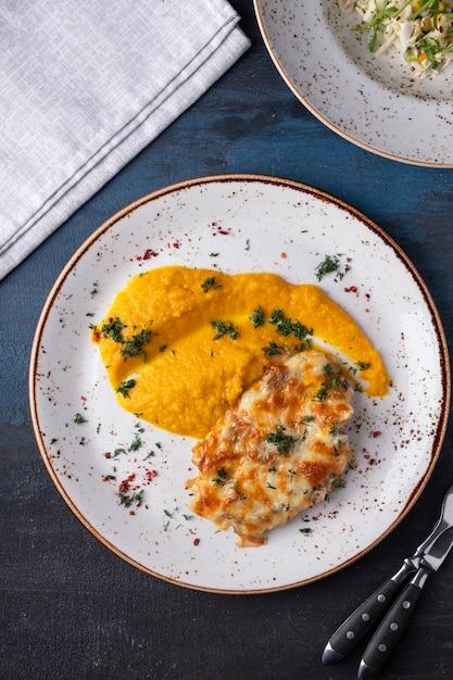 プレート上のチーズにんじんのピューレの下で焼きチキン。上面図 Premium写真
