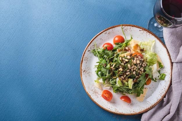 ルッコラのサラダチェリートマトと松の実のプレート。上面図。 Premium写真