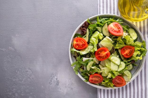 皿にサラダキュウリとフレッシュトマトの新鮮なミックス。健康とダイエット食品。上面図。 Premium写真