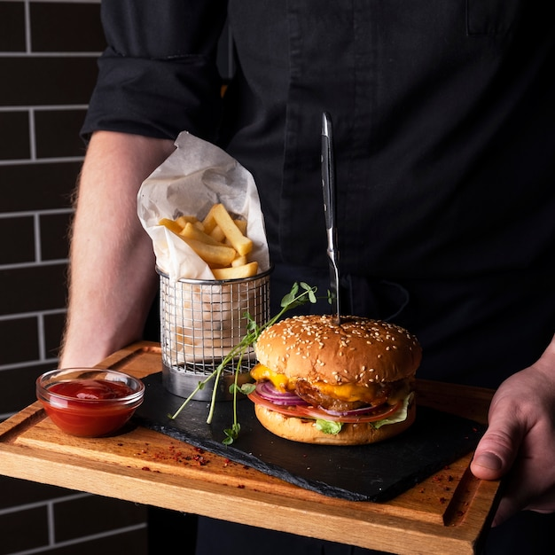 Сочный куриный бургер картофель на деревянной доске. Premium Фотографии