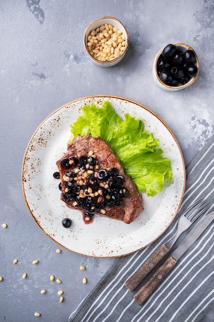 ローストミートブラックオリーブ、ナッツ、赤ソースのトップビューは、フォークとナイフを提供しています。飲食店の食べ物。 Premium写真