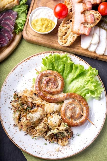 Сочные круглые жареные колбаски на деревянных шпажках с гарниром. вид сверху Premium Фотографии
