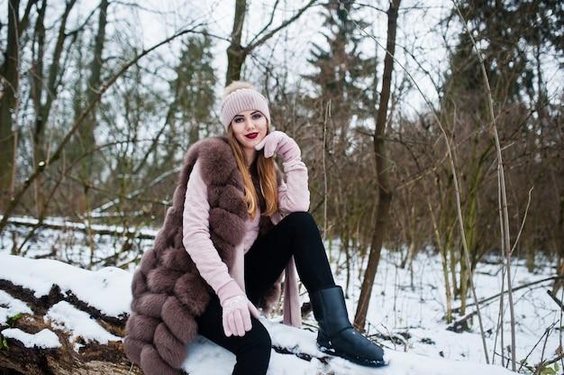 毛皮のコートと冬の森で帽子のスタイリッシュな女性。 Premium写真