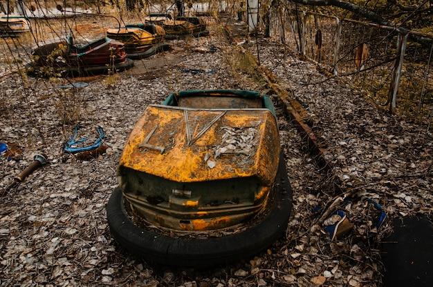 チェルノブイリの立ち入り禁止区域にあるプリピャチ市のさびた車で放棄された遊園地。 Premium写真