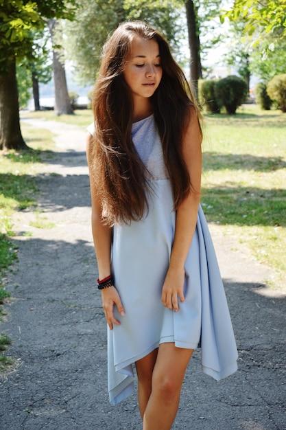 Портрет красивой девочки-подростка в синей блузке, против зеленой летней игры парка с ее волосами. Premium Фотографии