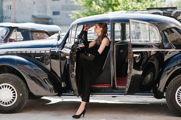 手にタバコを持つヴィンテージ車に座っているレトロなスタイルの明るいメイクと美しいセクシーなファッションの女の子モデルの肖像画。 Premium写真