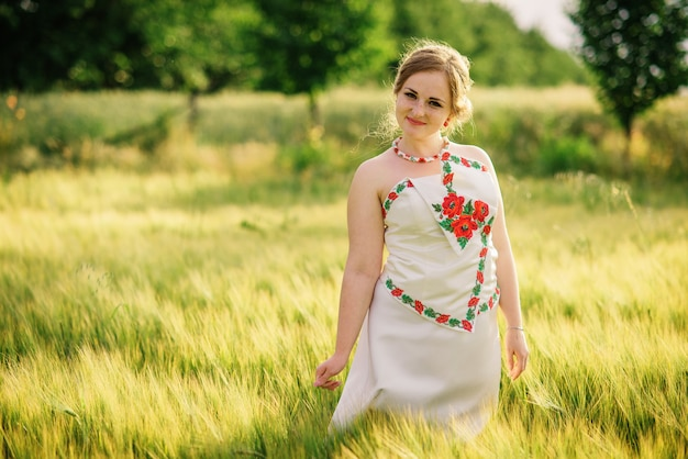 Маленькая девочка на украинском национальном платье представила на поле венка. Premium Фотографии