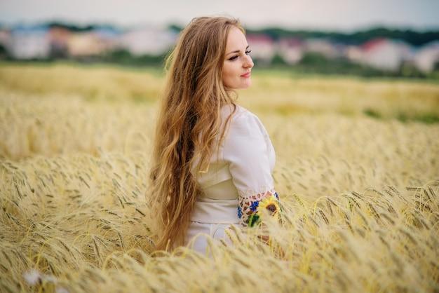 花輪のフィールドでポーズをとってウクライナの民族衣装で若い女の子。 Premium写真