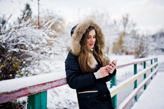 冬の暖かい服装で美しいブルネットの少女。公園で凍った湖に対する冬のジャケットのモデルは、携帯電話で話します。 Premium写真