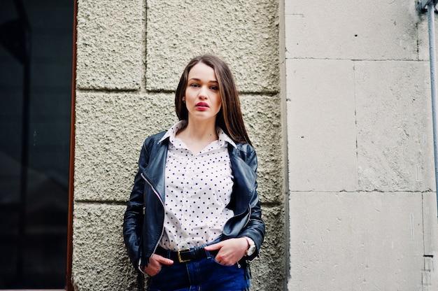 Портрет стильной молодой женщины в кожаной куртке и рваных джинсах на улицах города Premium Фотографии