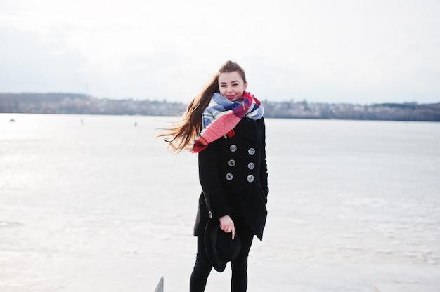 Случайные молодая девушка в черном пальто и шарф против замерзшей реки на солнечную зимнюю погоду. Premium Фотографии
