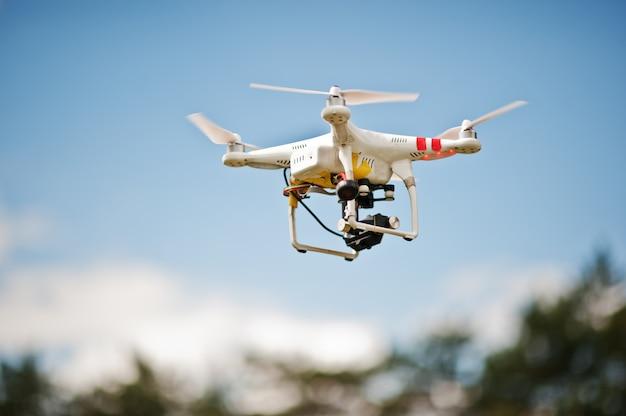 青い空を飛んでいる高解像度デジタルカメラとドローンクアッドヘリコプター Premium写真