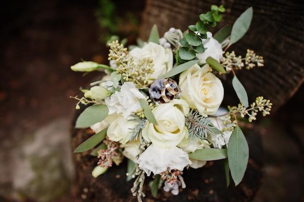 白いバラと木製の表面に敷設する他のハーブで作られたウェディングブーケのクローズアップ写真。 Premium写真
