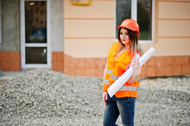 均一なチョッキとオレンジ色の保護ヘルメットのエンジニアビルダーの女性は、新しい建物に対してビジネス描画紙ロールを保持します。 Premium写真