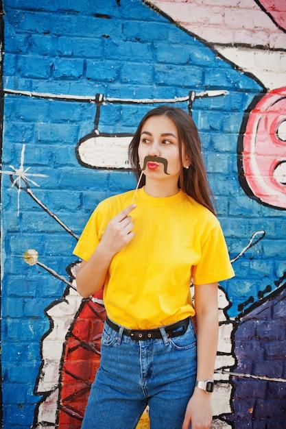 Красивая веселая девочка-подросток с бананом под рукой, носите желтую футболку, джинсы и усы на палочке возле граффити стены. Premium Фотографии
