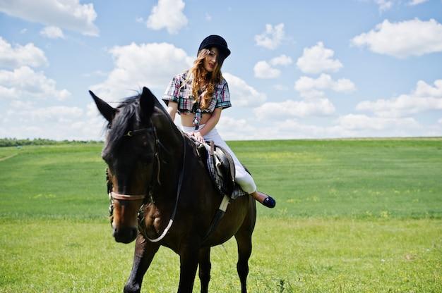 Молодая милая девушка ехать лошадь на поле на солнечном дне. Premium Фотографии