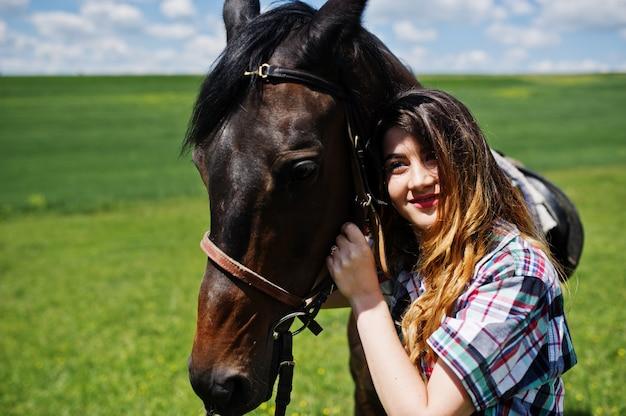 Молодое милое пребывание девушки с лошадью на поле на солнечном дне. Premium Фотографии