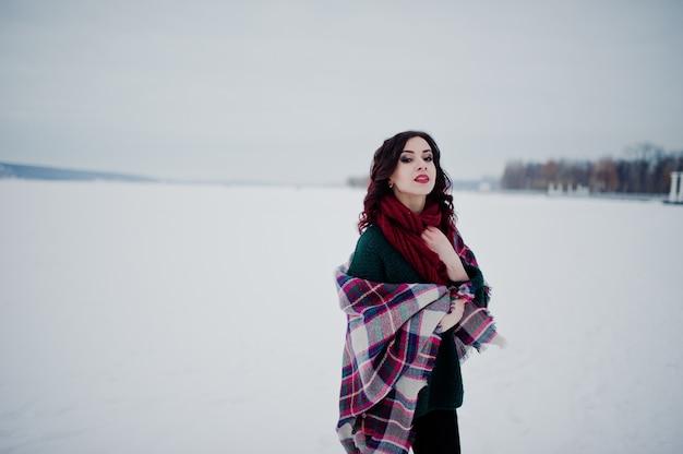 緑のセーターと夜の冬の日に格子縞の屋外凍った湖と赤いスカーフのブルネットの少女。 Premium写真