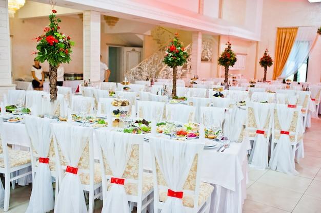 赤いリボンとレストランの椅子の上の白い結婚式の装飾 Premium写真