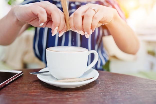 砂糖とコーヒーカップで手を閉じます。 Premium写真