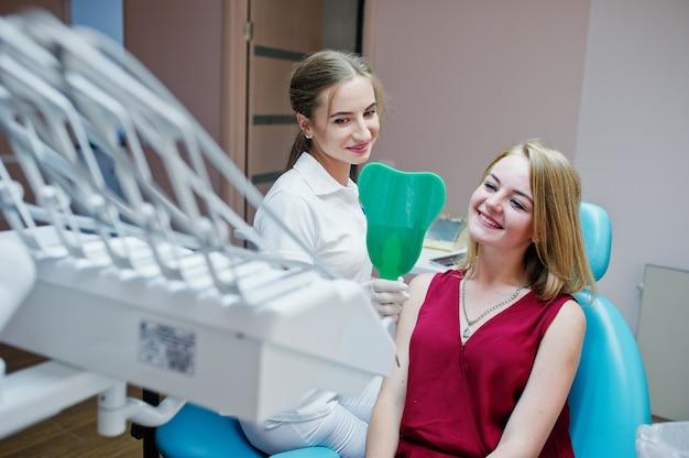歯科医のキャビネットの鏡を通して患者の新しい歯を見せている美しい歯科医。 Premium写真