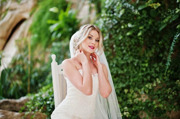 椅子に座って、素晴らしい素晴らしい結婚式場でポーズ豪華な金髪の花嫁 Premium写真