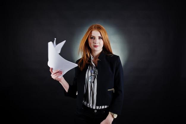 Портрет рыжеволосой бизнес-леди в полосатой блузке и куртке, выбрасывая бумаги. Premium Фотографии