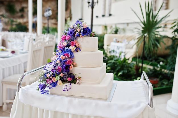 ホールで紫と紫の花のウェディングケーキ Premium写真