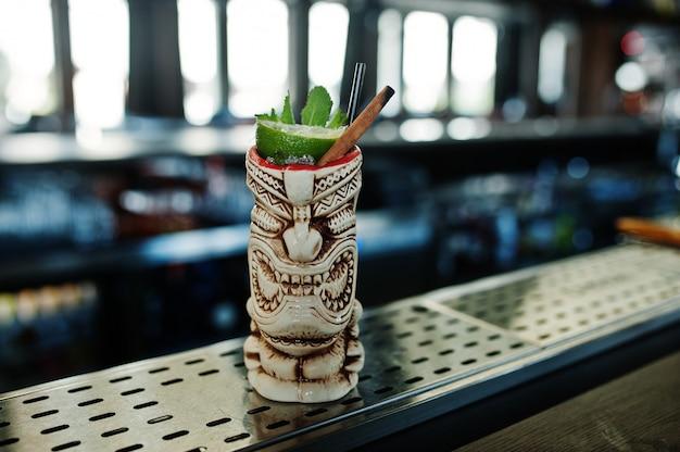 Алкогольный коктейль с мятой и лаймом в оригинальном вуду глиняном бокале на барной стойке Premium Фотографии