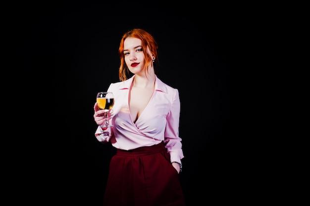 Шикарная красная с волосами девушка в розовой блузке и красной юбке с бокалом вина под рукой изолированной на черноте. Premium Фотографии