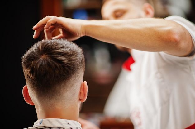 Молодой бородатый человек получая стрижку парикмахером пока сидящ в стуле на парикмахерскае. парикмахерская душа. Premium Фотографии
