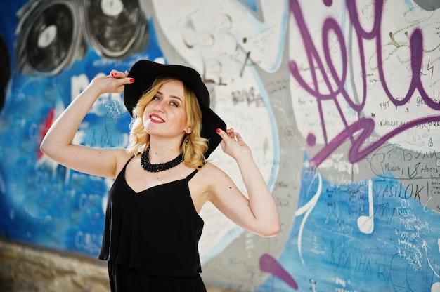 Белокурая женщина на черном платье, ожерельях и шляпе против граффити стены. Premium Фотографии