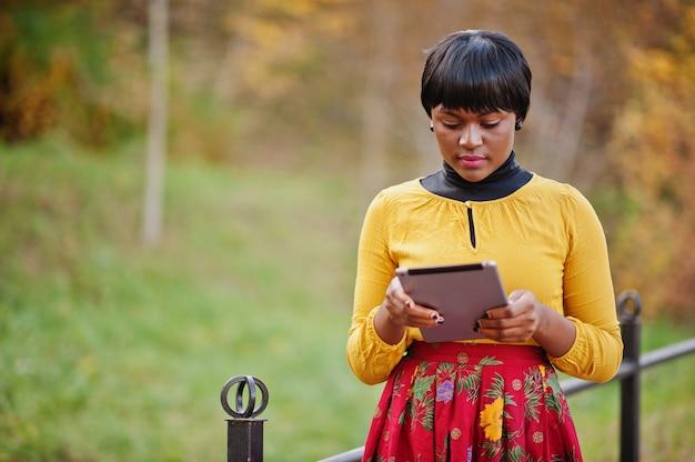 手でタブレットで黄金色の秋秋の公園で黄色と赤のドレスを着た女性 Premium写真