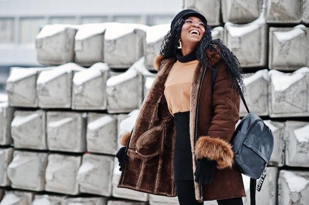 Афро-американская женщина в дубленке и кепке представляла в зимний день на снежном каменном фоне. Premium Фотографии
