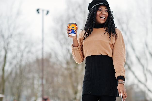Афро-американская женщина в черной юбке, коричневом свитере и кепке позирует в зимний день на снежном фоне, держа чашку кофе Premium Фотографии